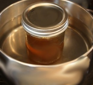 Honey in a pot of hot water. Crystallized honey can be liquefied.