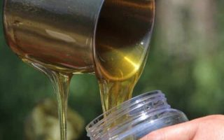 pouring raw honey into a jar