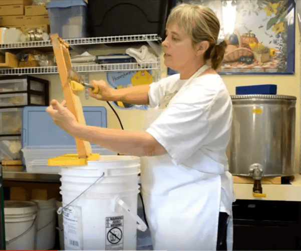 beekeeper is uncapping beeswax during honey harvest
