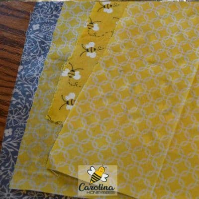4 finished beeswax food wraps laying on table