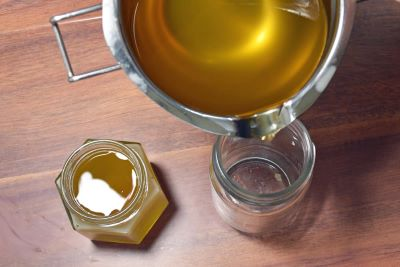 pouring beeswax furniture polish recipe into glass jars to cool