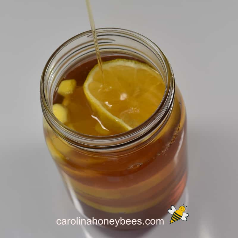 pouring honey into lemon and ginger jar for infusion