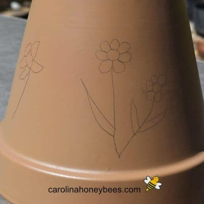 picture of a penciled flower design on painted clay pot