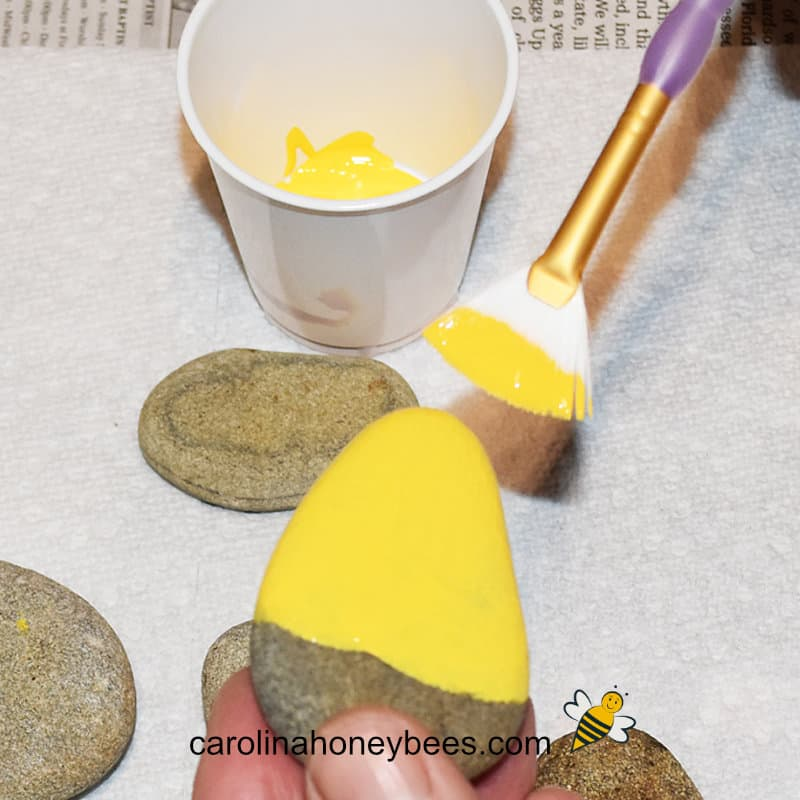 river rock painted yellow for base coat of bee