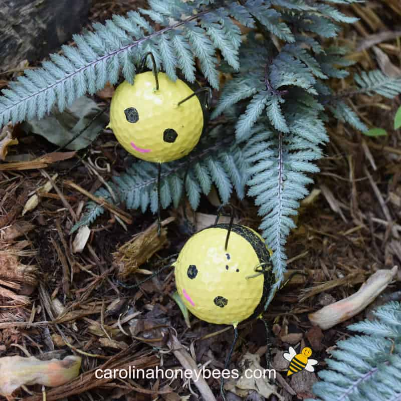 painted golf ball bee craft in a garden