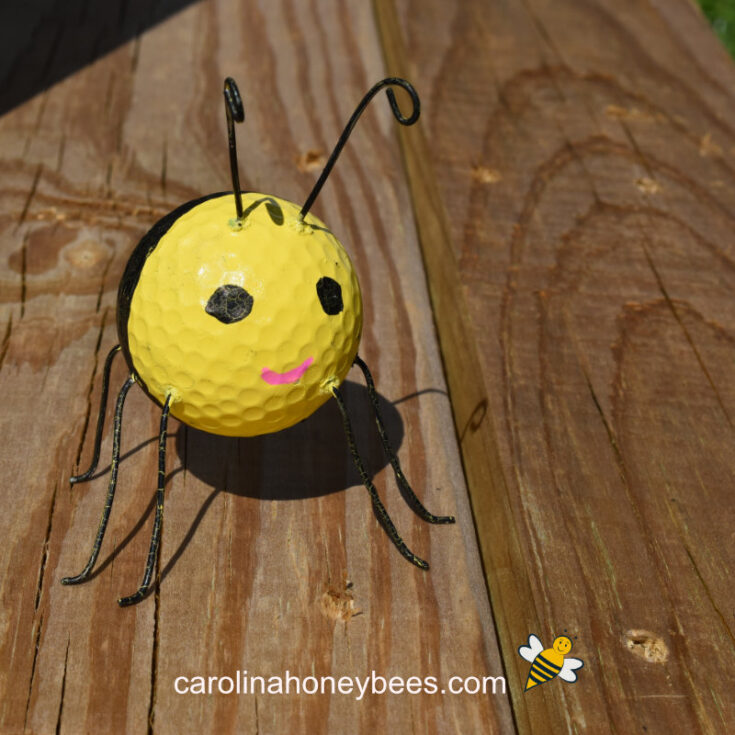 bee created using an old golf ball, wire and paint