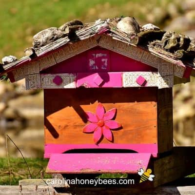 image of a brightly painted bee hive in the old style