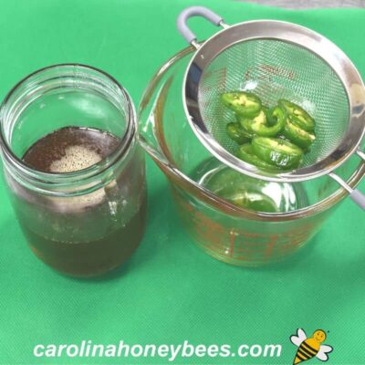 Jalapeno slices strained from warm honey image.