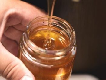 freshly harvested honey pouring into a glass jar