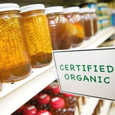 shelf of honey jars in grocery with organic label