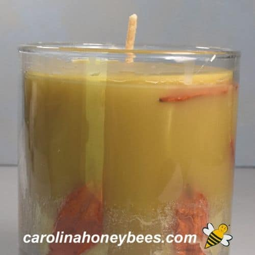 Finished candle in glass jar trimmed beeswax wick image.