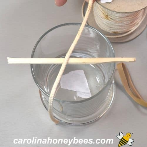 candle jar with craft stick and wick measured