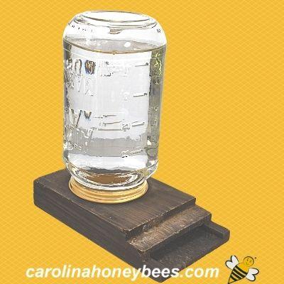 mason jar bee feeder on wooden base