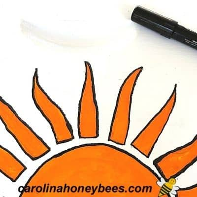 sun design painted on bee hive box