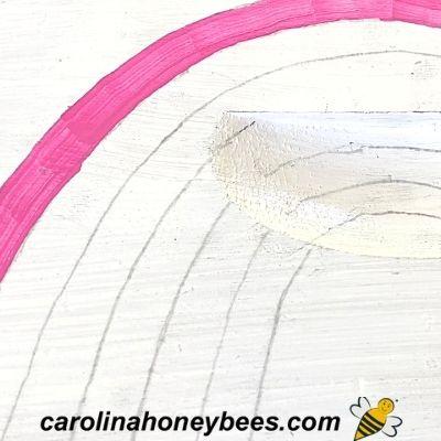 painting rainbow design on bee hive box