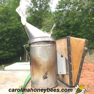 Bee smoker with cool white smoke coming from nozzle image.