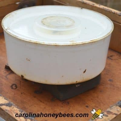 Round bee feeder to be used feeding bees inside the hive image.