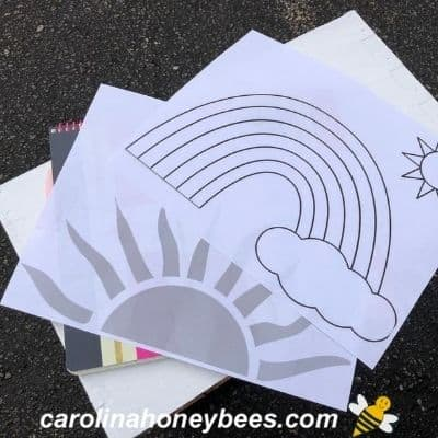 printed simple design outlines of sun and rainbow