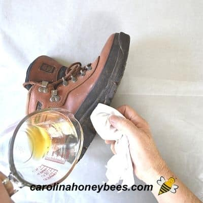 applying coat of melted bees wax to boot leather to seal out water