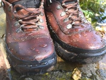 old hiking boots with beaded water drops after beeswax waterproofing