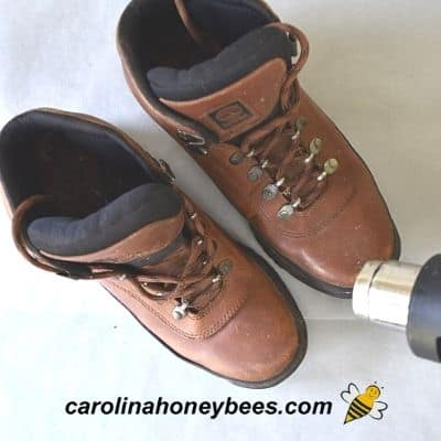 Using heat gun to warm leather boots before waterproofing with beeswax image.