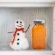 snow man in freezer with frozen jar of honey