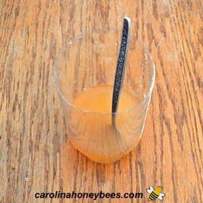 Mixing sugar and vinegar in plastic bottle half image.