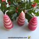 image of handmade rolled beeswax Christmas tree candles with Holly