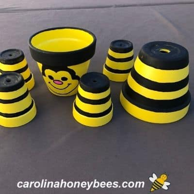 picture of parts of clay bee project with black strips on pots