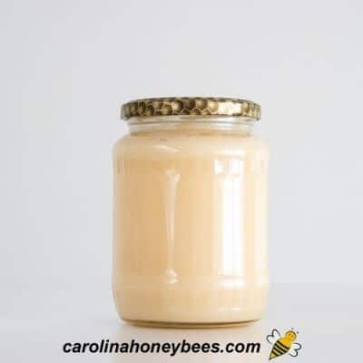 White jar of crystallized honey with lid before liquified image.
