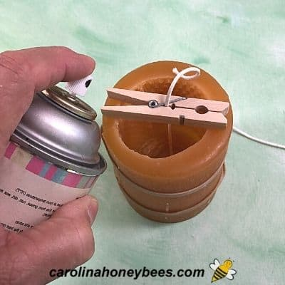 Spraying mold release into a silicone beeswax candle mold image.