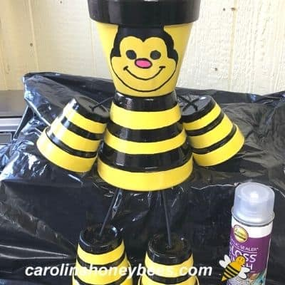 picture of assembled clay pot honey bee being sprayed with clear sealer