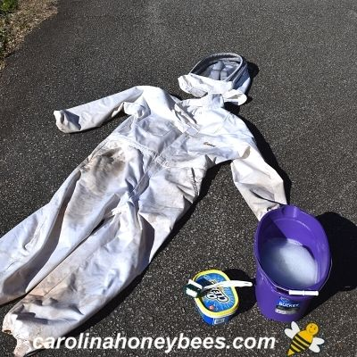 Dirty beekeeping suit being treated with bucket of stain remover prior to washing image.