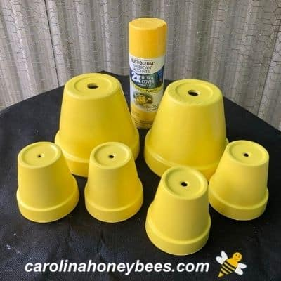 picture of 6 clay pots painted yellow for bee base coat
