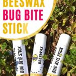 Containers of beeswax bug bite sticks laying in grass diy image.