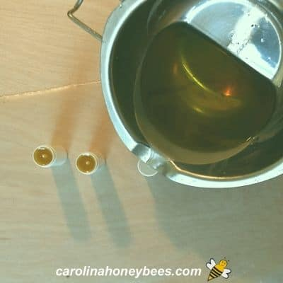 Pouring melted bug stick recipe into lip balm tubes image.