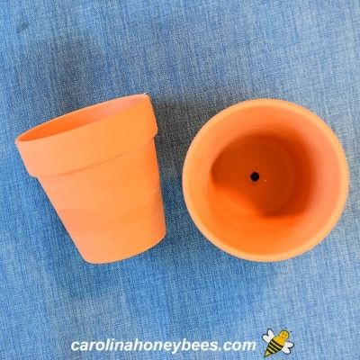 Two small clay pots for candle making image.