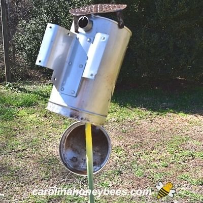 Drying bee smoker on a stake in the yard image.