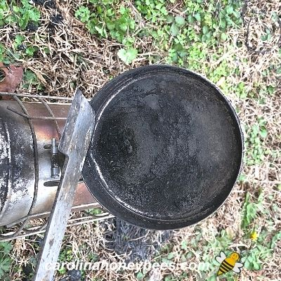Cleaning bee smoker lid with hive tool image.
