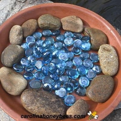 Natural river stone and glass stones in a clay dish for bee water image.