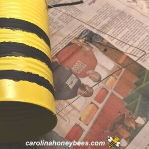 Wire hanger glued to tin can bee image.