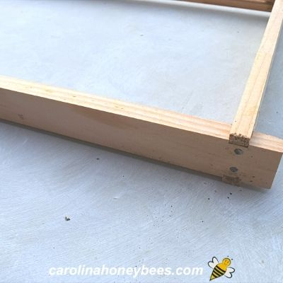 Small nails assemble top bar to end bar of frame image.