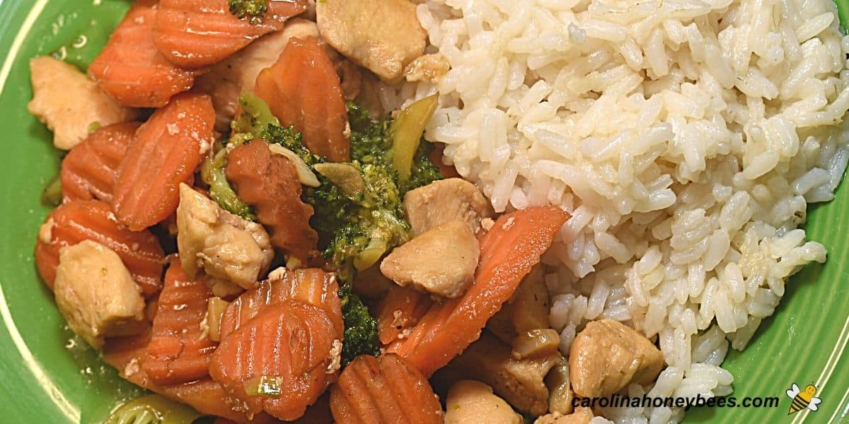 Honey chicken stir fry with vegetable on plate image.