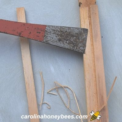 Using hive tool to scrape excess wood from top bar image.