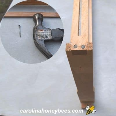 Hammer, small nail and wooden frame image.