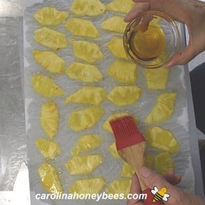 Brushing light coat of honey on pineapple prepared for dehydration image.