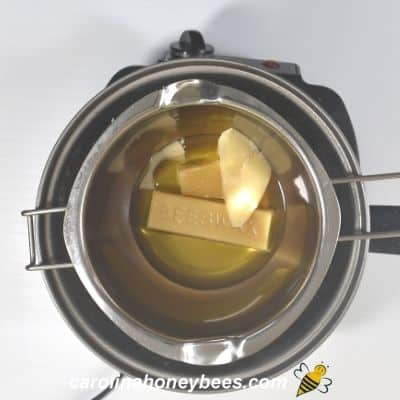 Melting beeswax in double boiler for making tarts image.