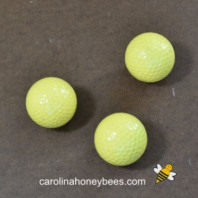 Base coat of yellow painted on 3 golf balls image.