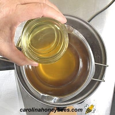 Adding coconut oil to melted beeswax for spoon butter image.