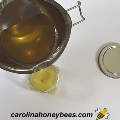 Pouring beeswax vapor rub recipe into containers image.